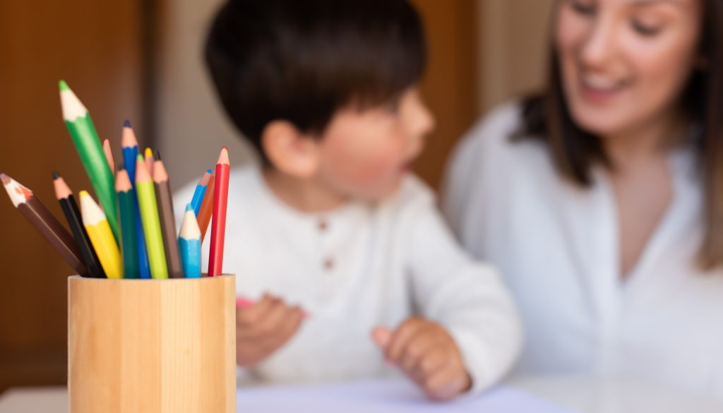 Preschooler kid drawing with coloured pencils with mother or tea